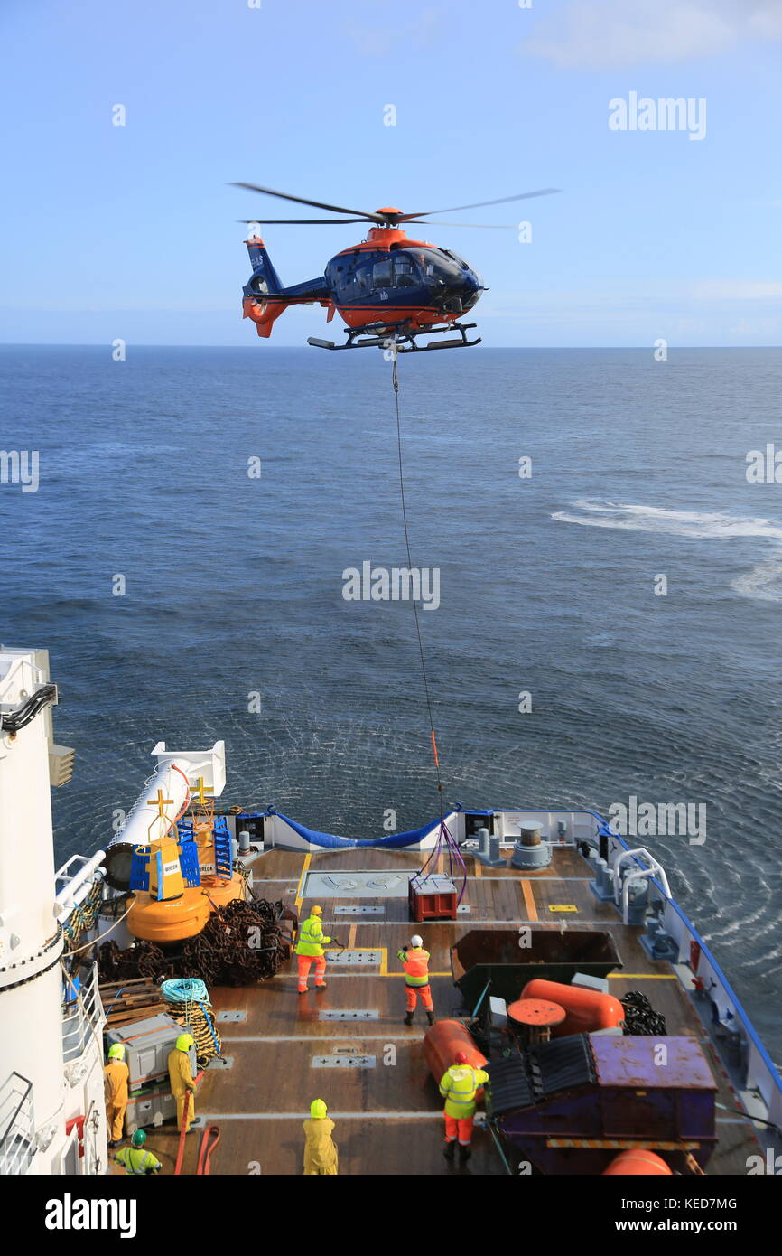 Helicopter moving cargo on Large sea vessel - Stock Image