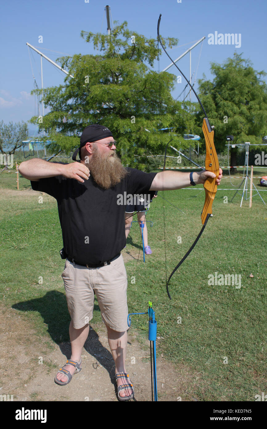 Mann mit langem Bart und Shorts beim bogen schießen - Stock Image