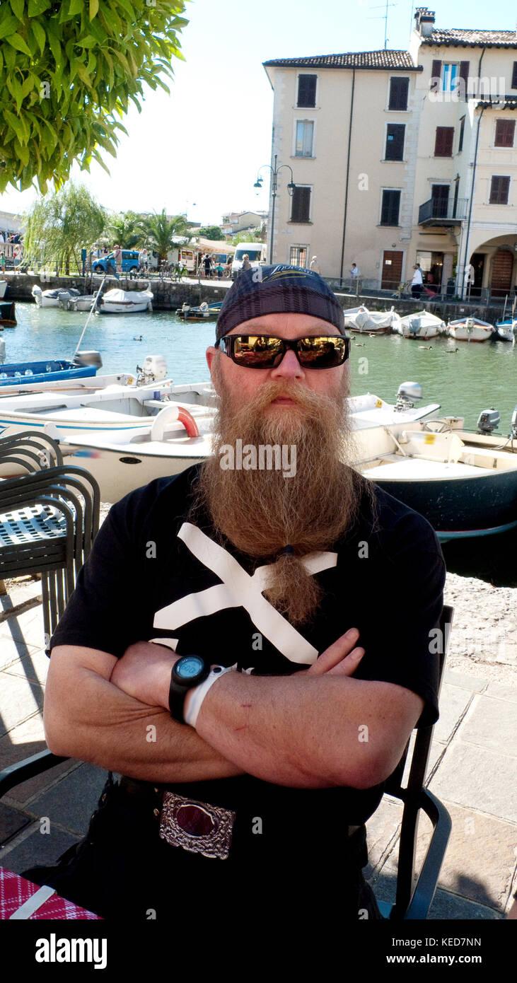 MAnn mit langem Bart und Sonnenbrille am Gardasee bei Descenzano - Stock Image