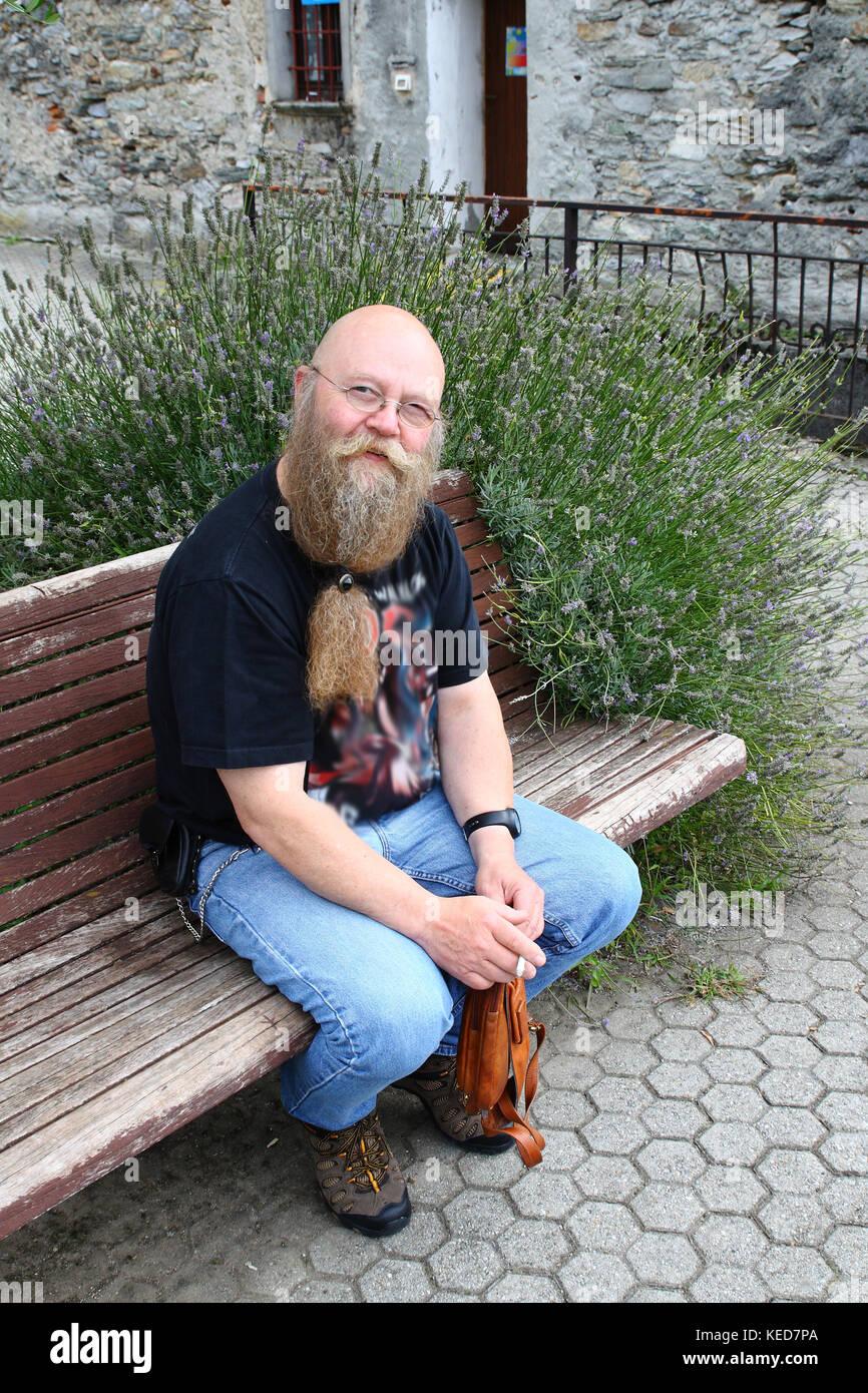 Ein Mann mit langem Bart sitzt auf einer Sitzbank - Stock Image