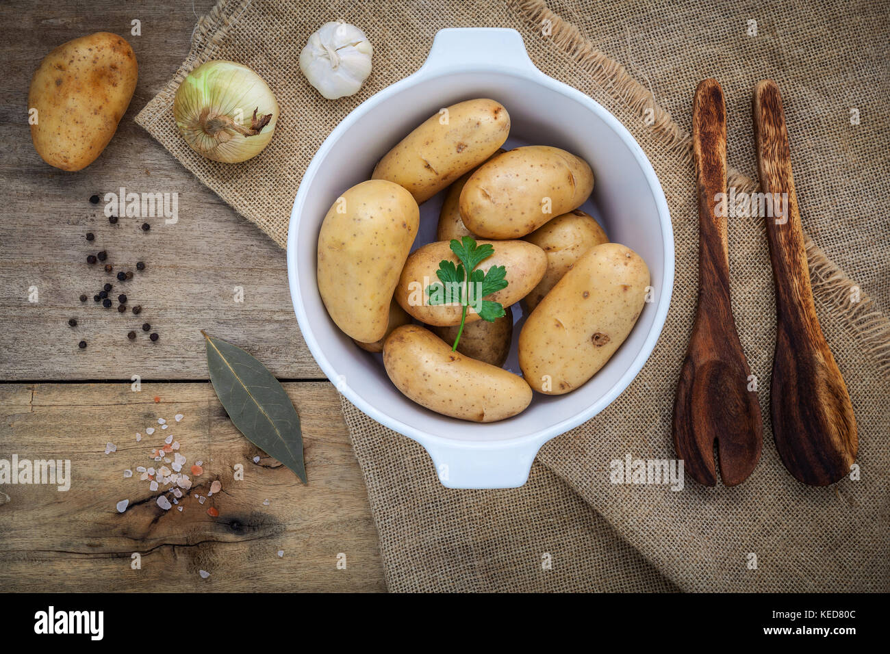 Fresh organic potatoes in white ceramic bowl with ingredients and herbs  , parsley, garlic, bay leaves, pepper, - Stock Image