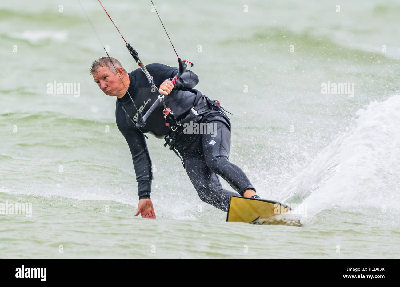 Man performing a turn while kitesurfing at sea on a windy day. Male kitesurfer on the ocean. - Stock Image