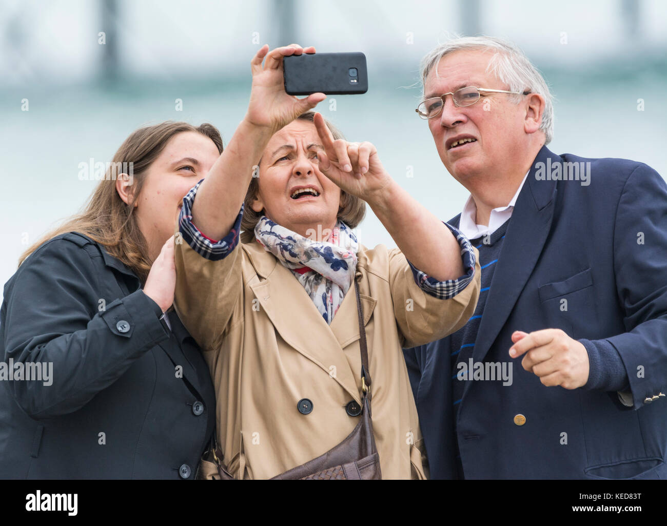 Elderly people struggling with technology while trying to take a family selfie. - Stock Image