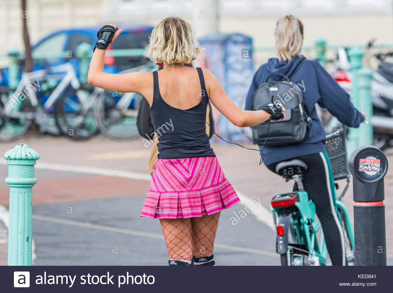 Woman dancing while roller skating in a cycle lane in Brighton, East Sussex, England, UK. - Stock Image