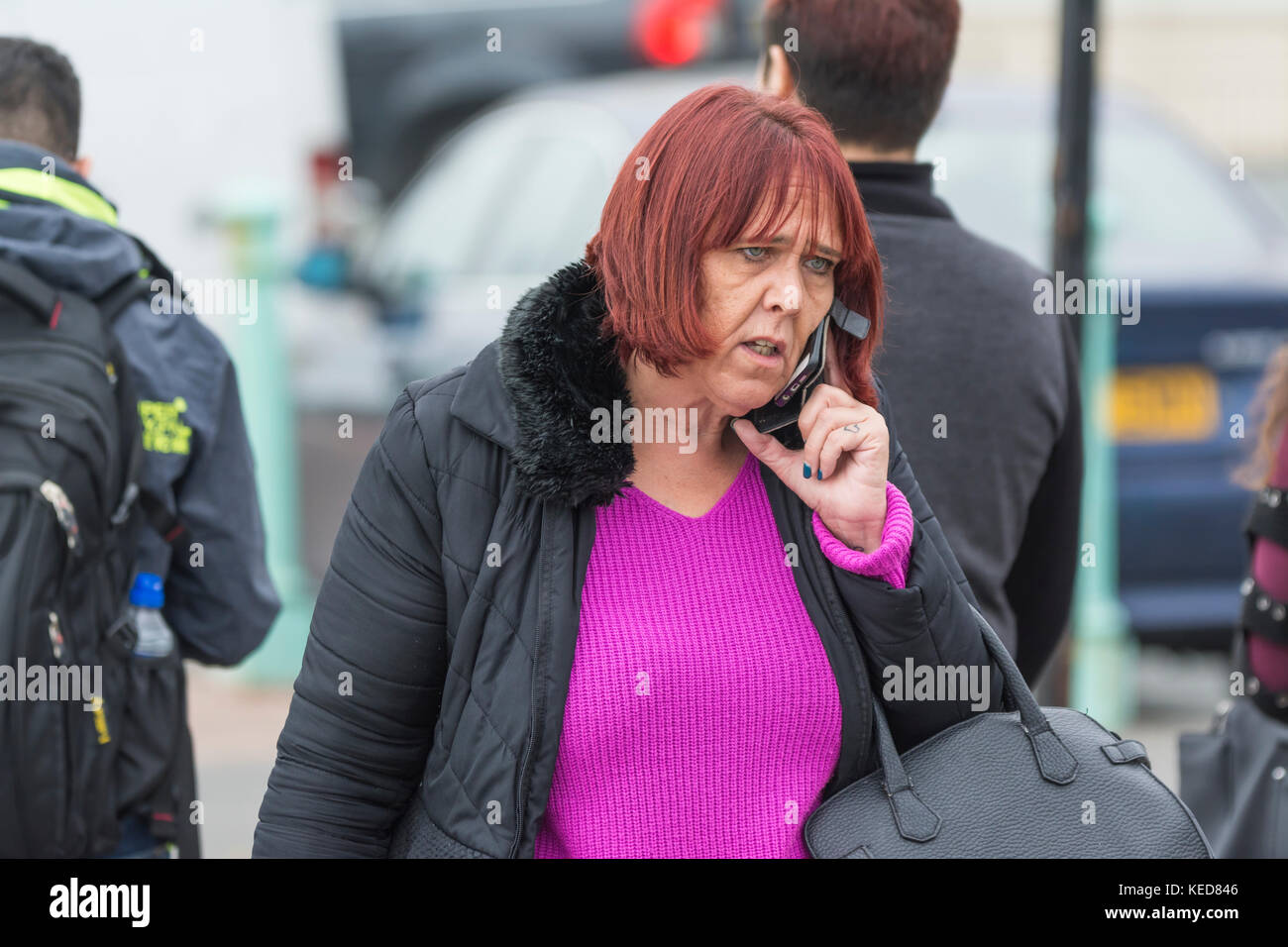 Middle aged woman speaking on a mobile phone while walking outside in the UK. - Stock Image
