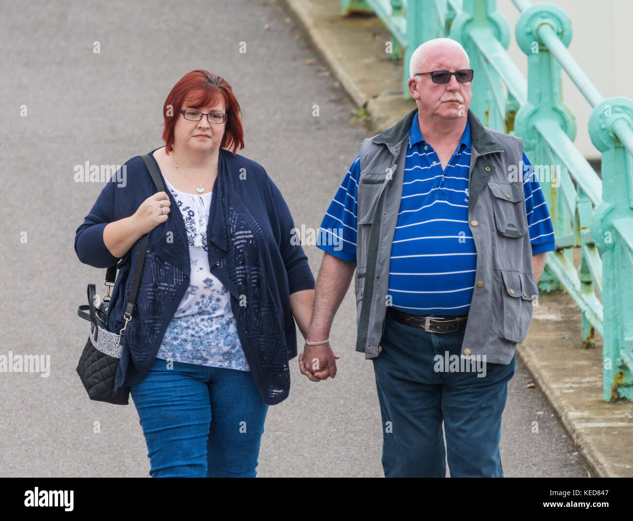 A couple with a large age difference holding hands. - Stock Image