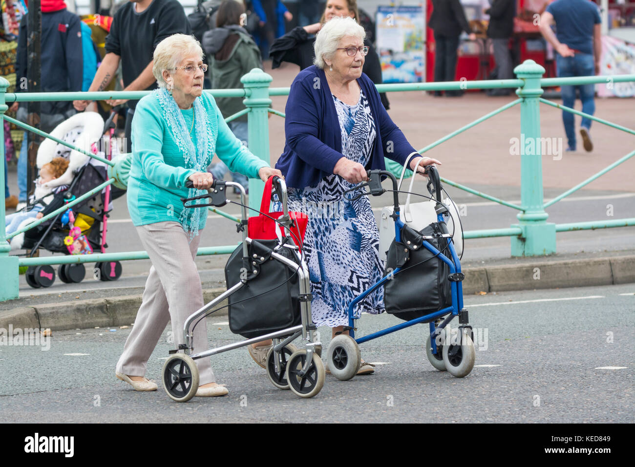 Elderly women crossing a road with wheeled walkers in Brighton, East Sussex, England, UK. Zimmer frame. Rollator. - Stock Image