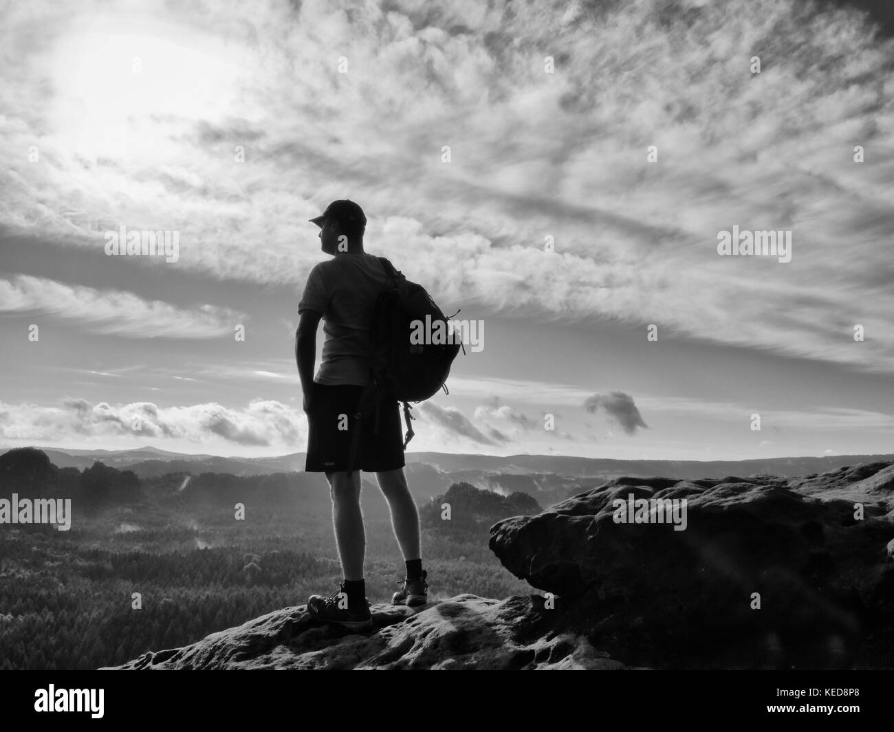 Alone tourist with red  baseball cap sporty backpack stand on cliff edge and watching into deep valley bellow. Spring - Stock Image