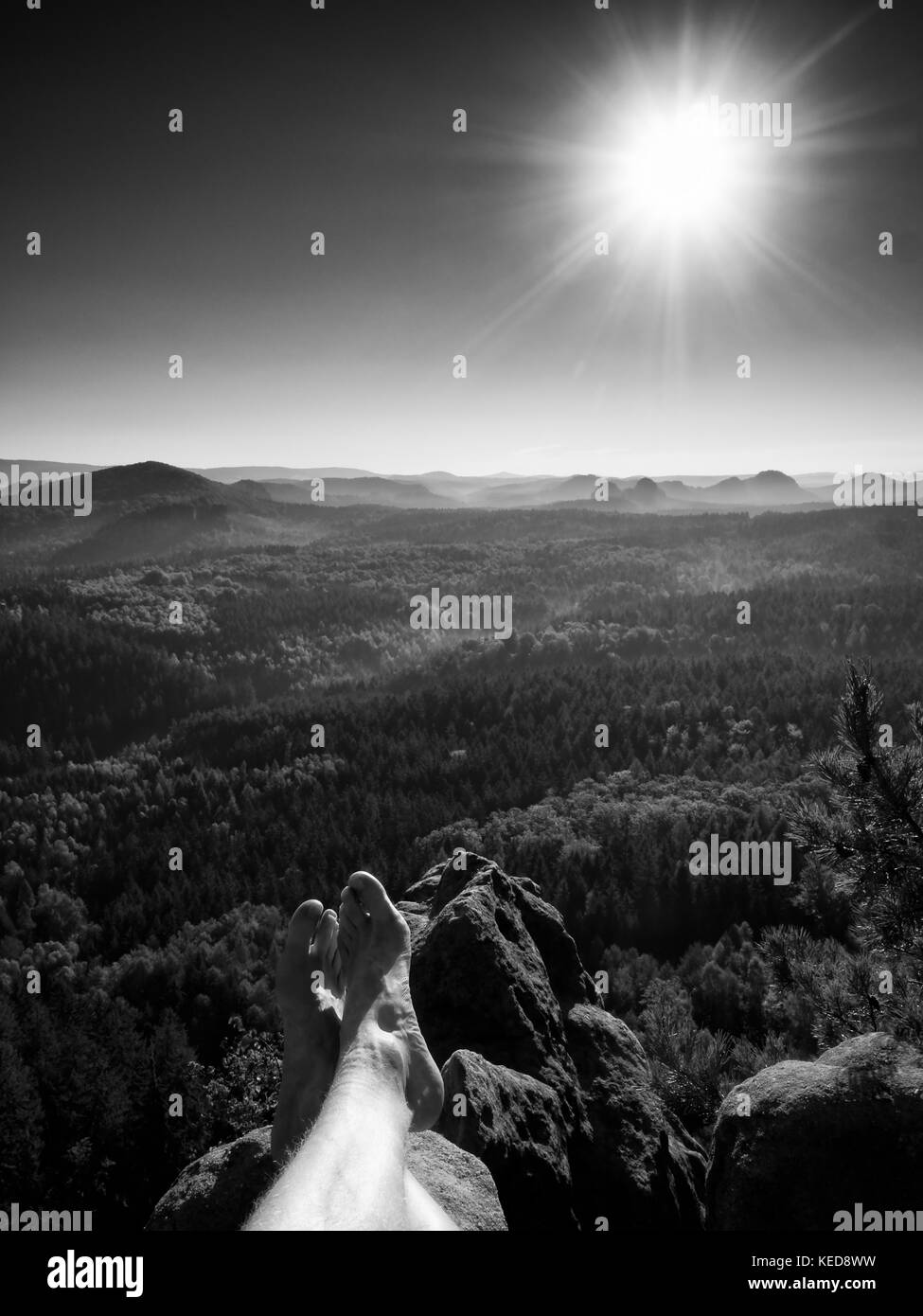 Tired legs take a rest on peak of rock. Trekking trip in hot summer weather. Long forest valley in hilly landscape - Stock Image
