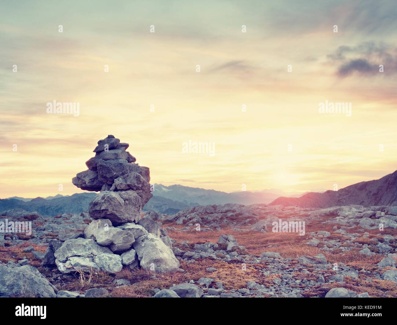 Sharp stones stacked at trail run. Heavy pebbles stack on dry grass on mountain at trekking path, evening orange - Stock Image