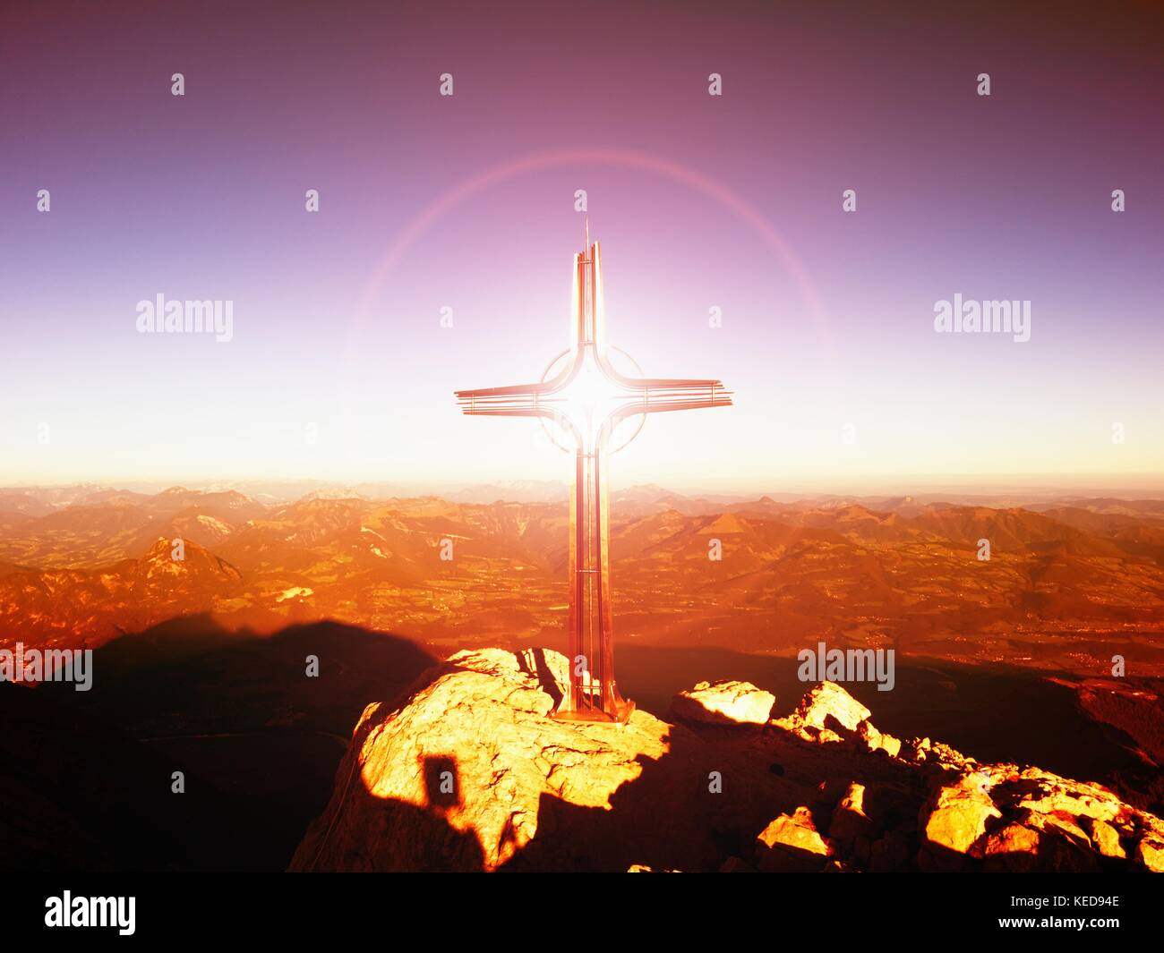 Lens flare light, strong effect.  Cross on peak of Hoher Goell. Iron crucifix at mountain top in Alp at Austria Stock Photo