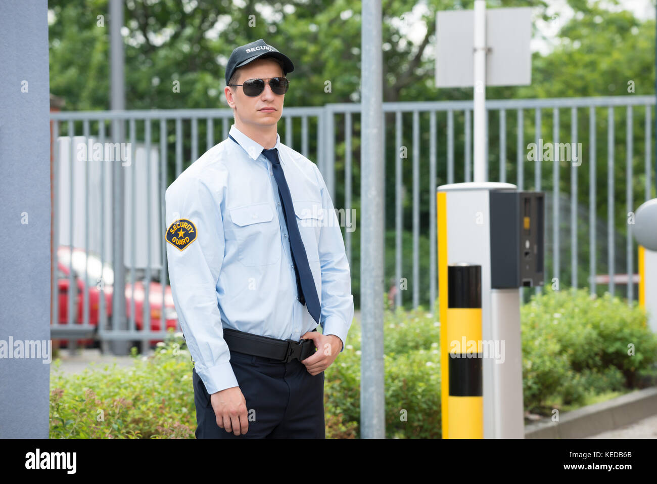Young Male Security Guard Standing Beside Car Parking Machine - Stock Image