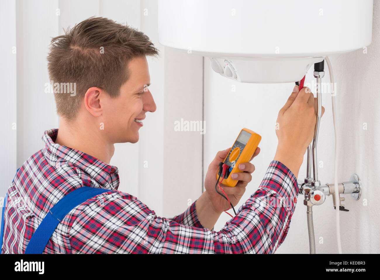 Smiling Male Plumber Examining Electric Boiler With Multimeter Probe - Stock Image