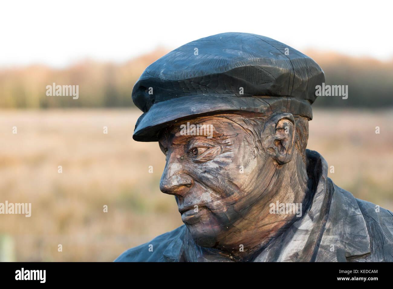 lifesize wooden sculpture of lifelike miner - Stock Image