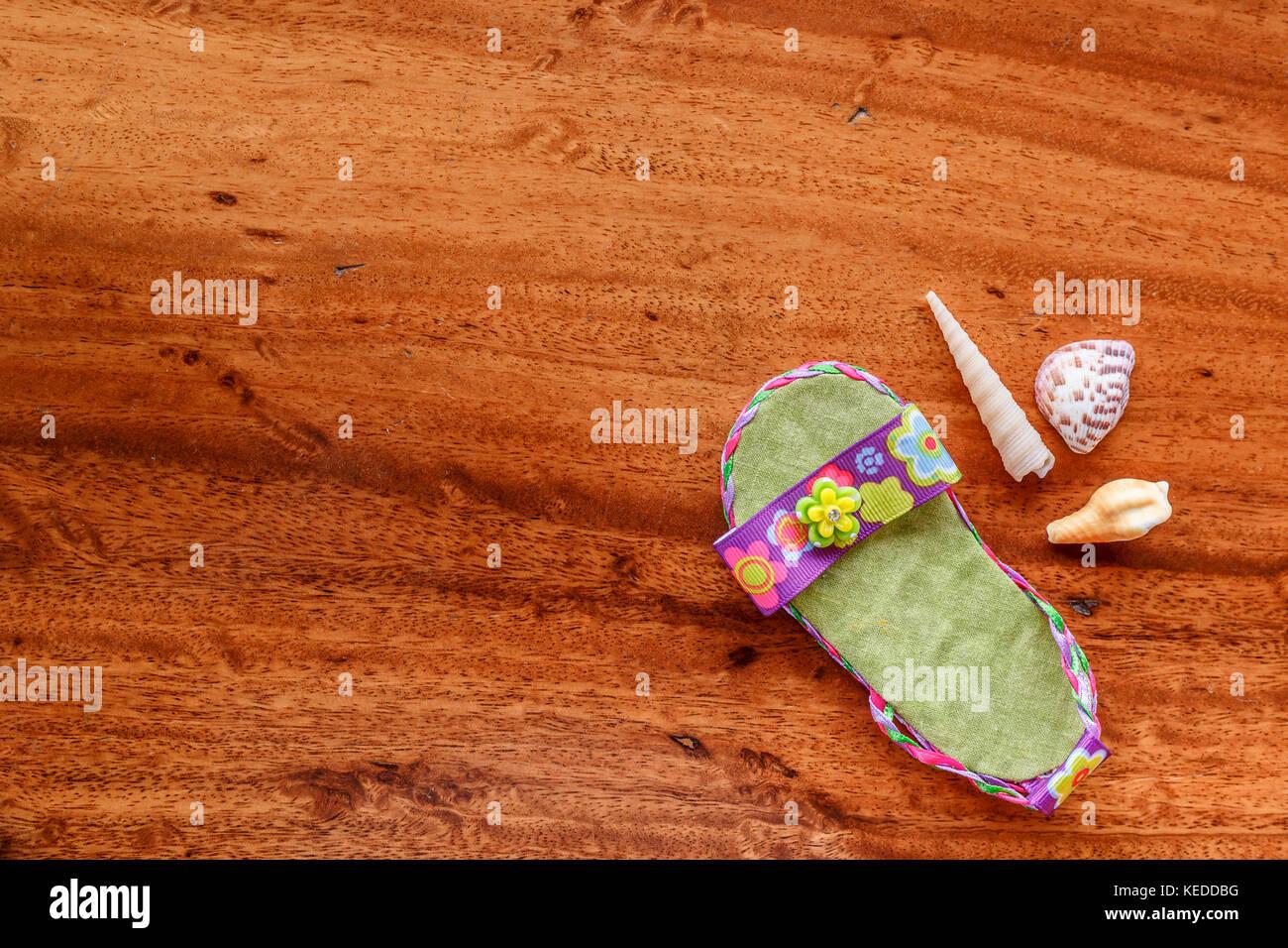 Purple baby sandal with seashells arranged on a wood grain background. Minimalist style appearance - Stock Image