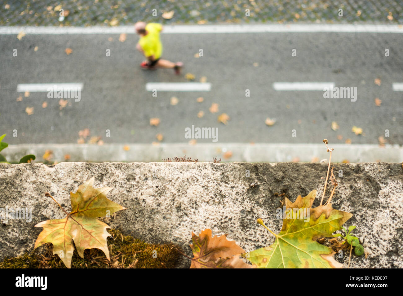 -Selective Focus- View from above, defocused/blurred person with a yellow t-shirt  is running on a pedestrian track. Stock Photo
