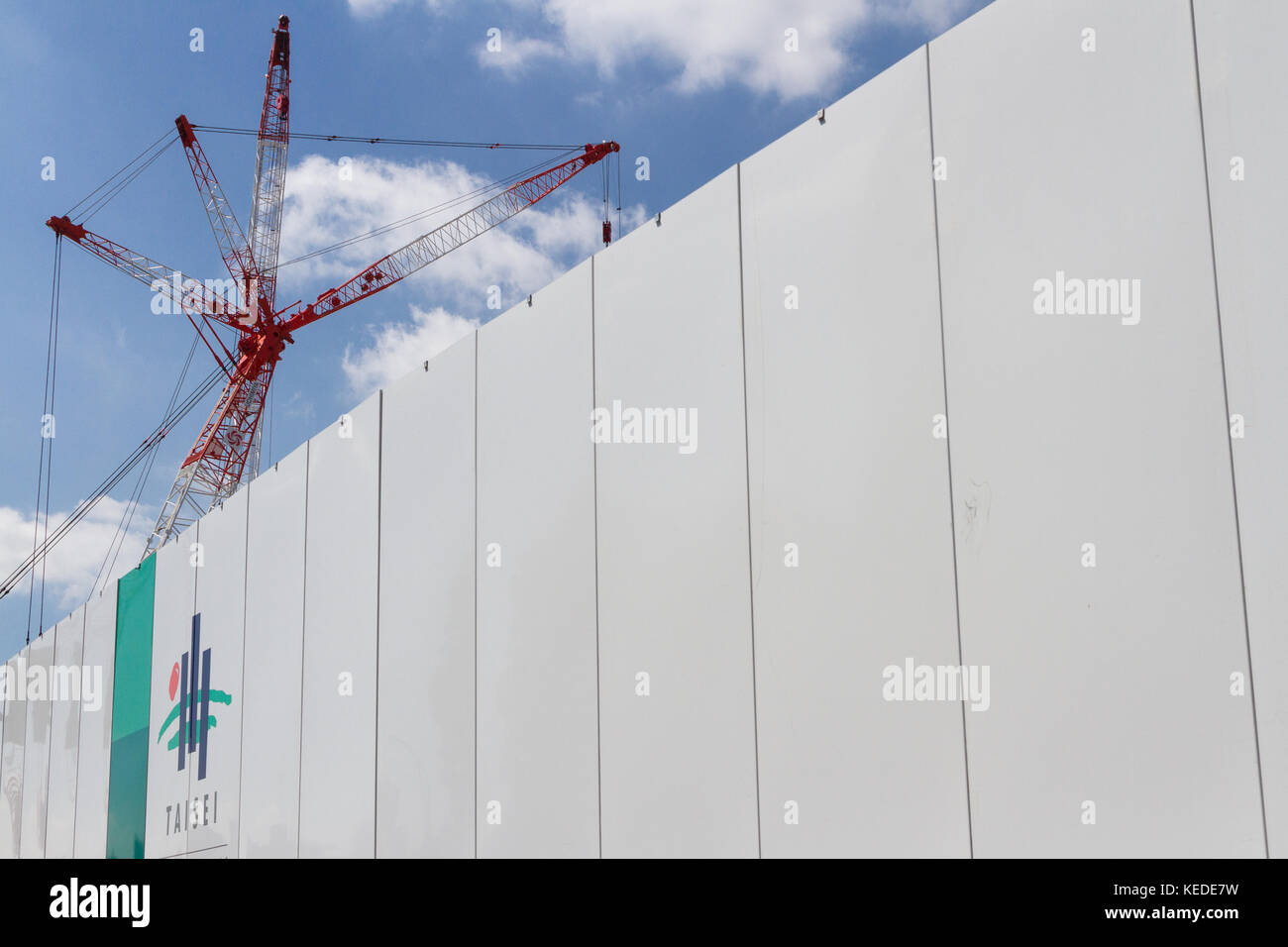 A cane above a wall with the Taisei Construction company name and logo on it at the construction site of the new - Stock Image