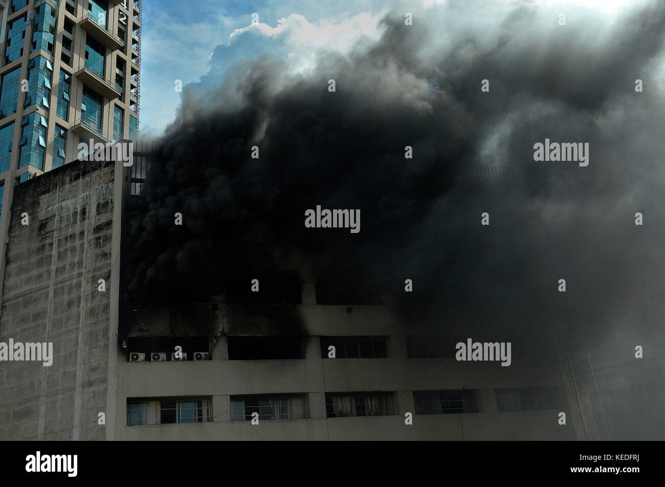 Kolkata, India. 18th Oct, 2017. Smoke and flames come out from the window after a high rise office building caught - Stock Image
