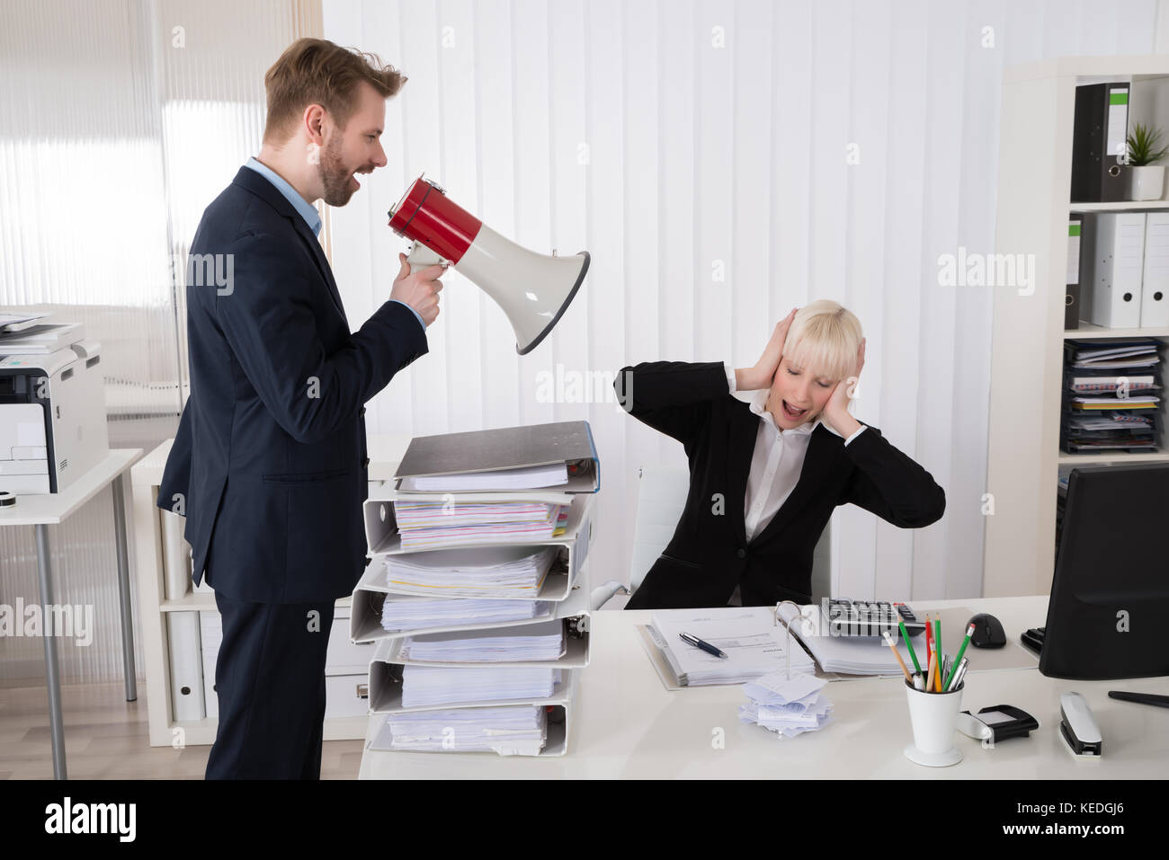 Boss Shouting At Young Businesswoman Through Loudspeaker In Office Stock Photo