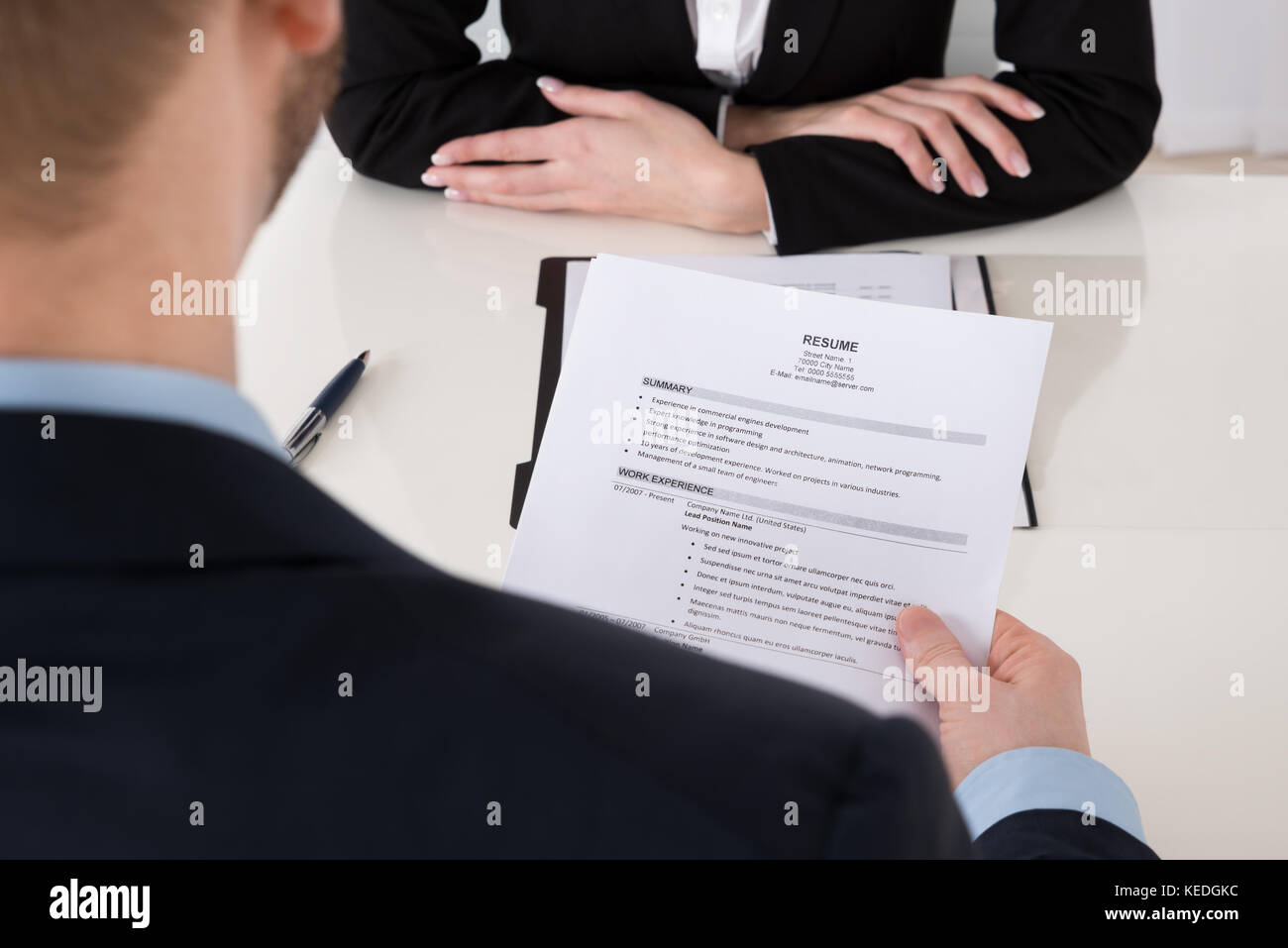 Close-up Of Young Businessman Holding Resume At Office Desk - Stock Image