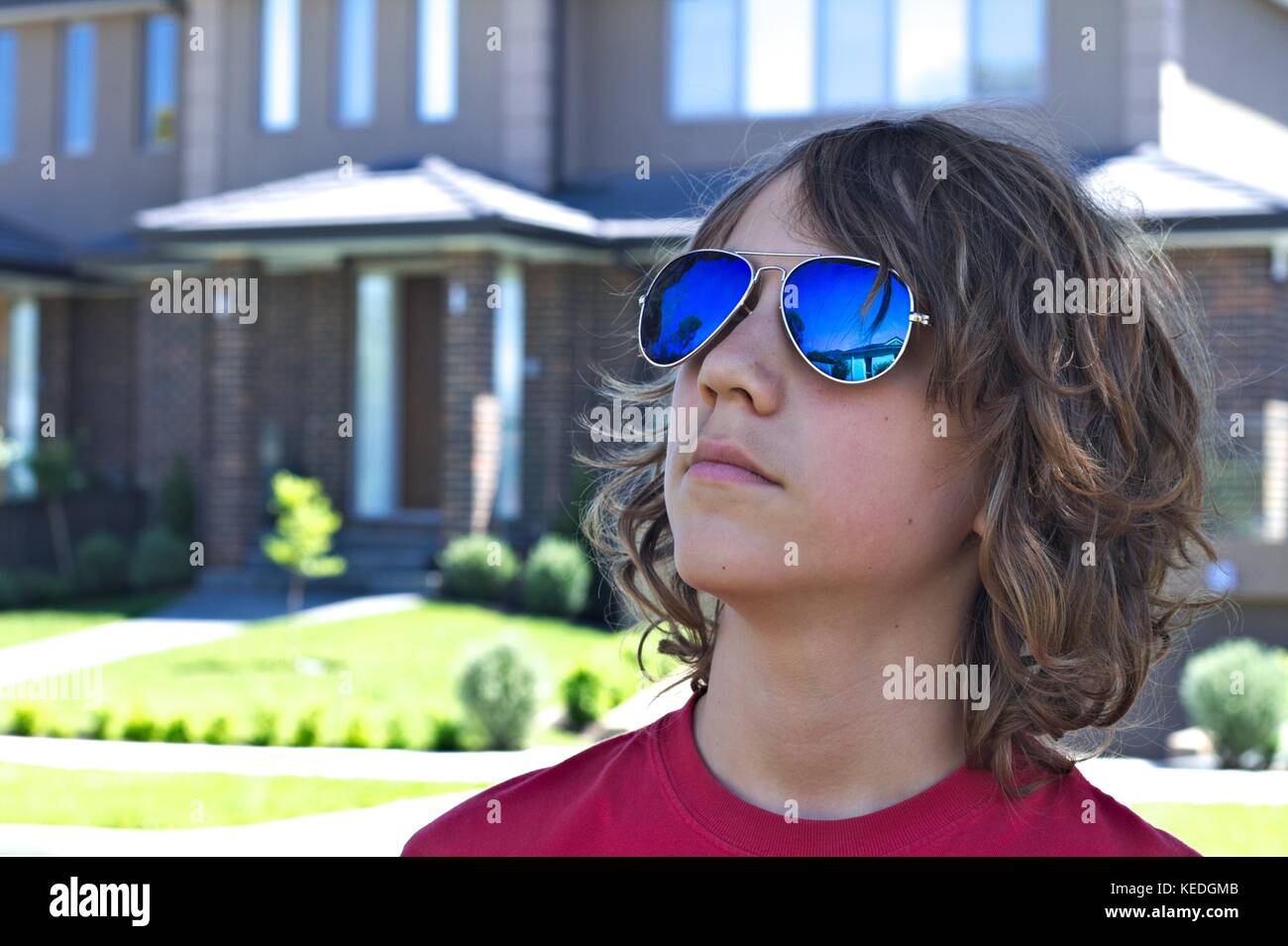 Young teenage male wearing blue sunglasses head shot against suburban background. Stock Photo