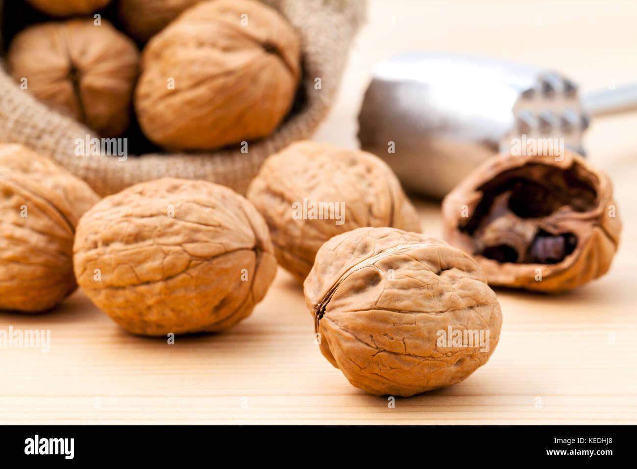 Walnuts kernels and whole walnuts on wooden background. Whole and chopped walnuts on wooden background. Walnuts - Stock Image