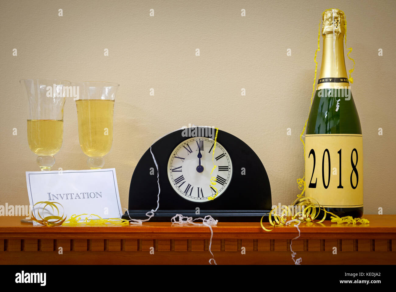 a clock showing midnight at new year with a bottle of champagne labelled 2018 glasses and invitation surrounded by streamers