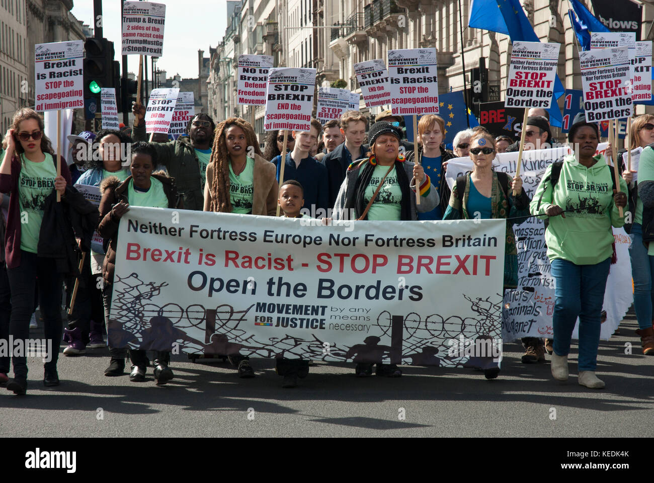 Demonstrators anti Brexit, pro EU, many posters and large banner' Open the Borders, Brexit is rascist' - Stock Image