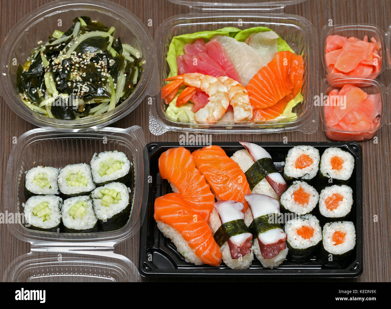Takeaway Japanese food assortment on wooden table - Stock Image