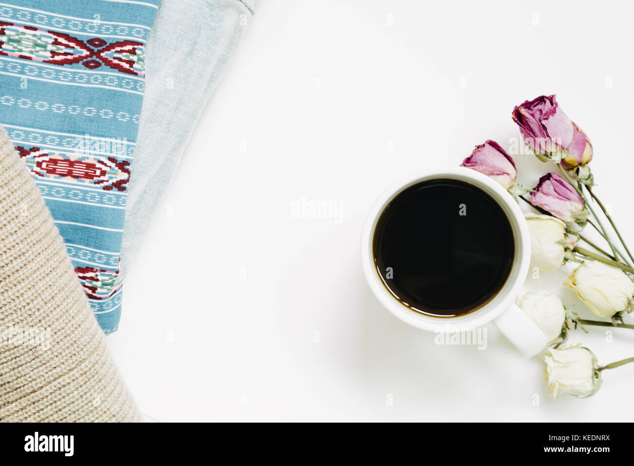 cup of coffee and dry rose flowers and vintage clothes isolated on white background. top view - Stock Image