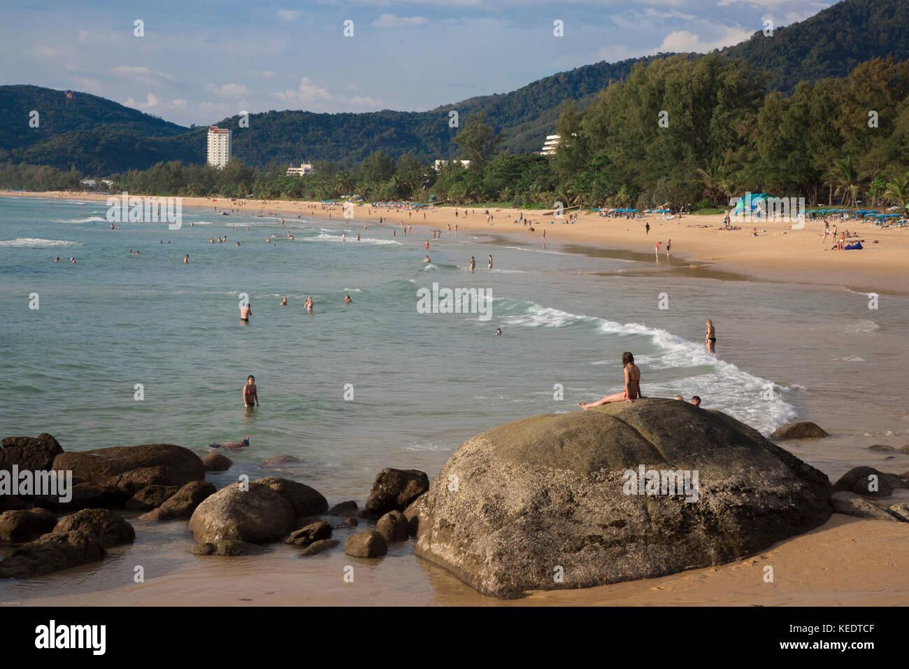 Tourists swimming and relaxing on Karon Beach, Phuket Island, Thailand - Stock Image