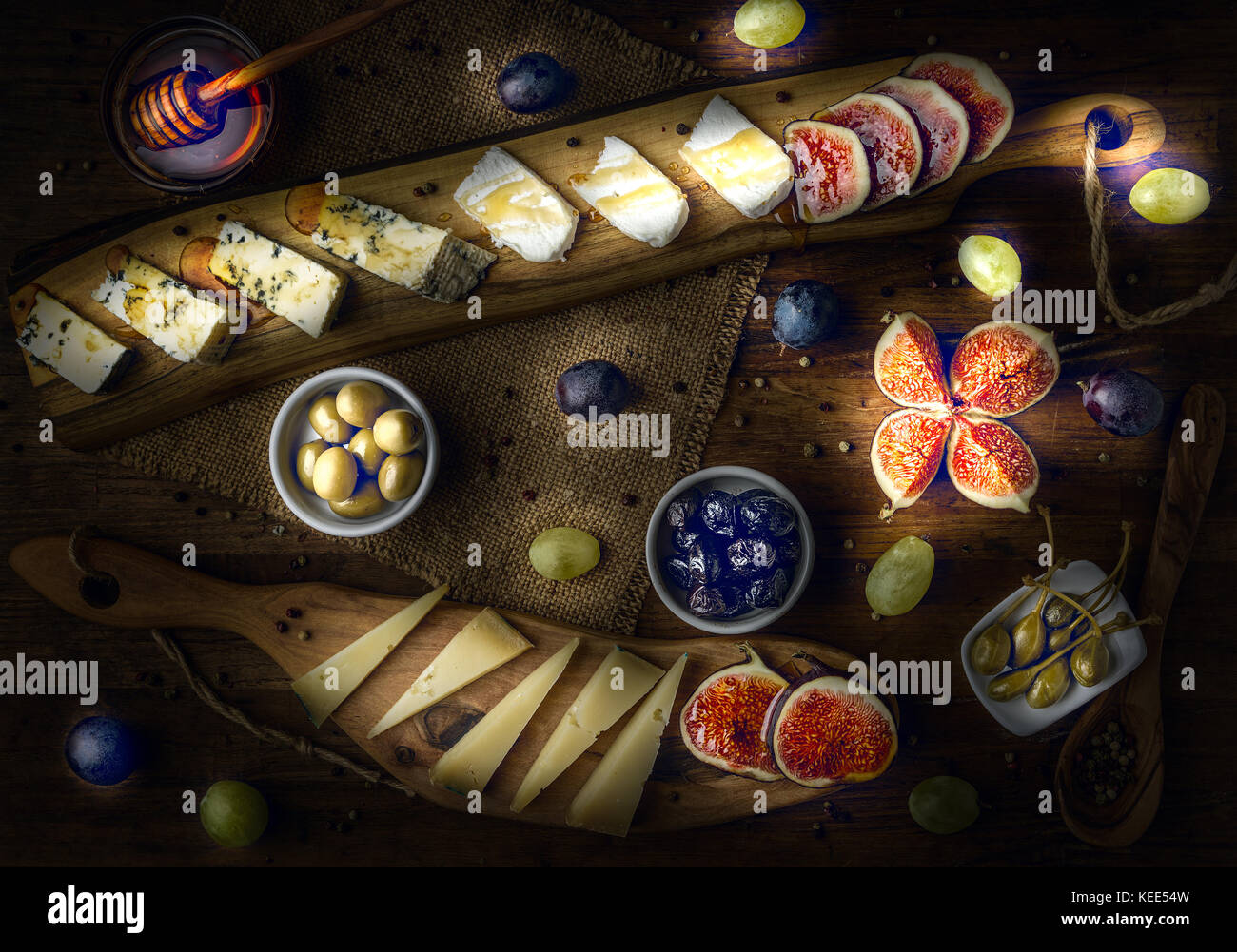 platter of italian cheeses with figs, olives, grapes and honey toned ightpainted - Stock Image