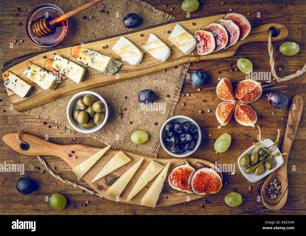 platter of italian cheeses with figs, olives, grapes and honey toned - Stock Image