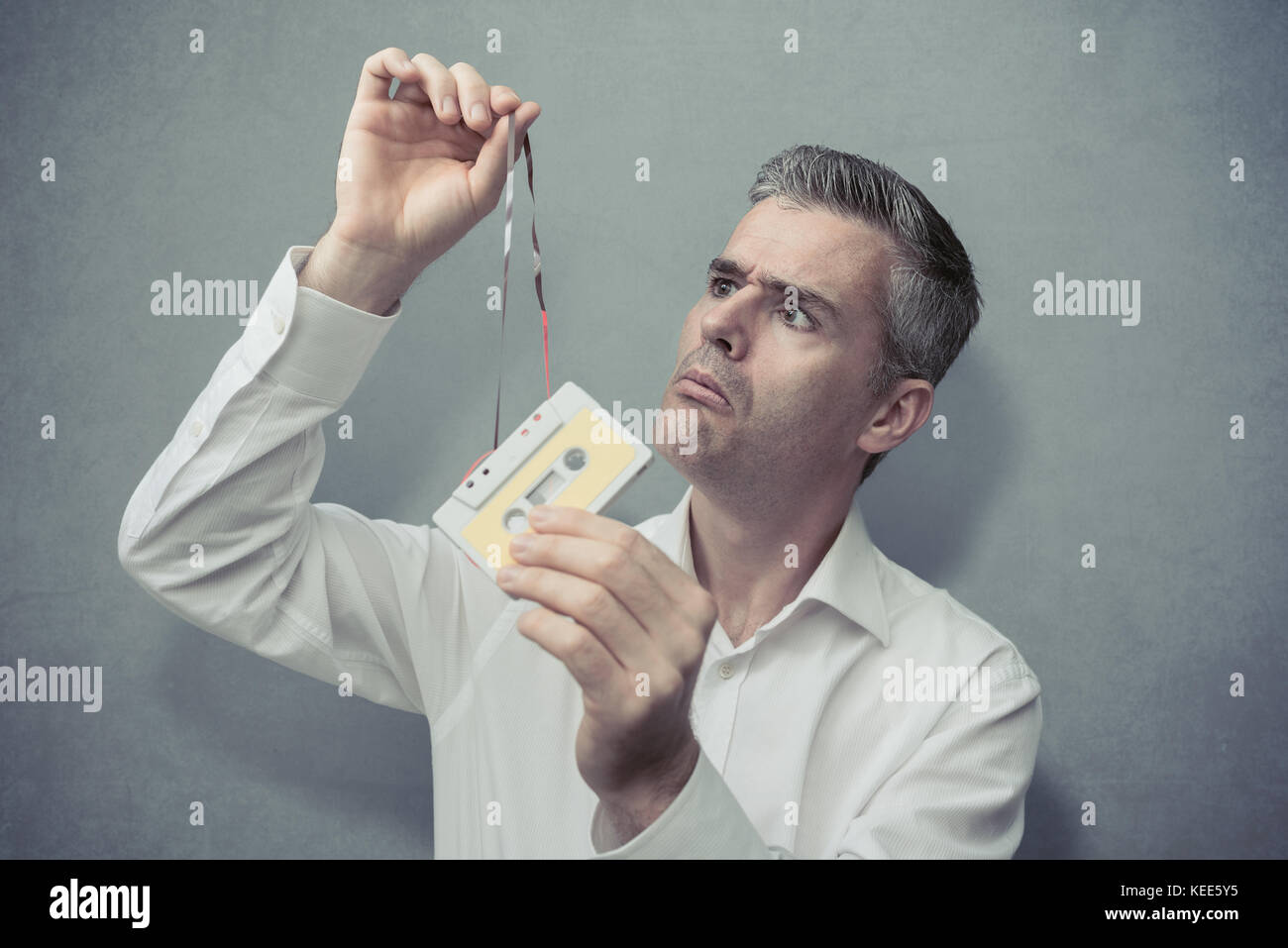 Clueless confused man holding an old audio cassette and pulling the tape, vintage outdated technology concept - Stock Image