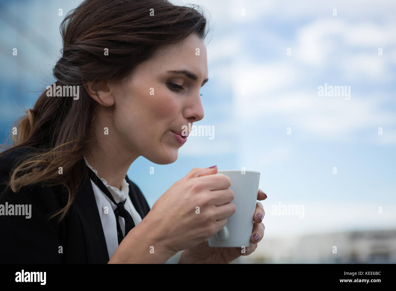 Young female executive having coffee in office premises - Stock Image