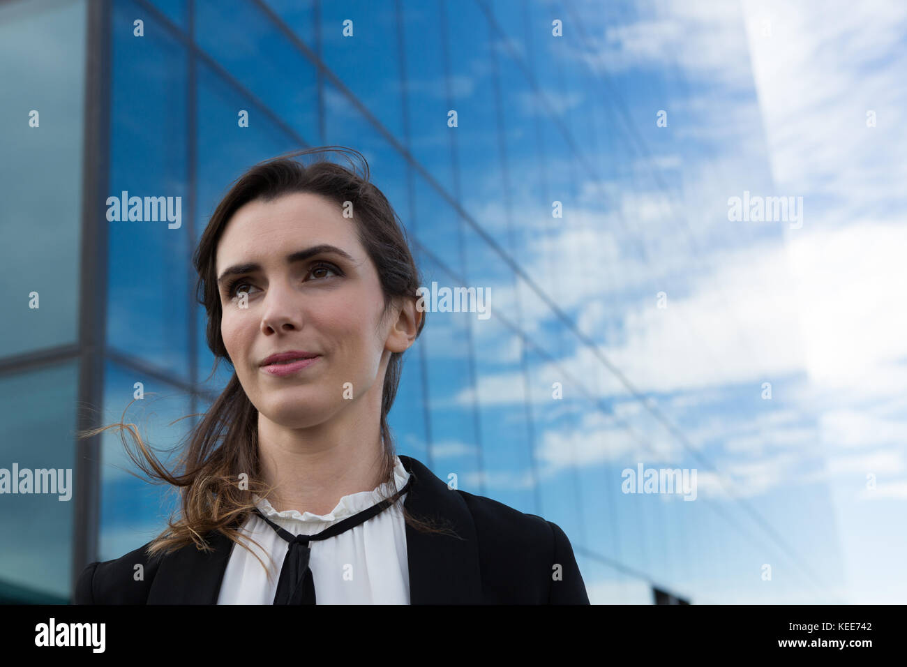 Young female executive standing in office premises - Stock Image