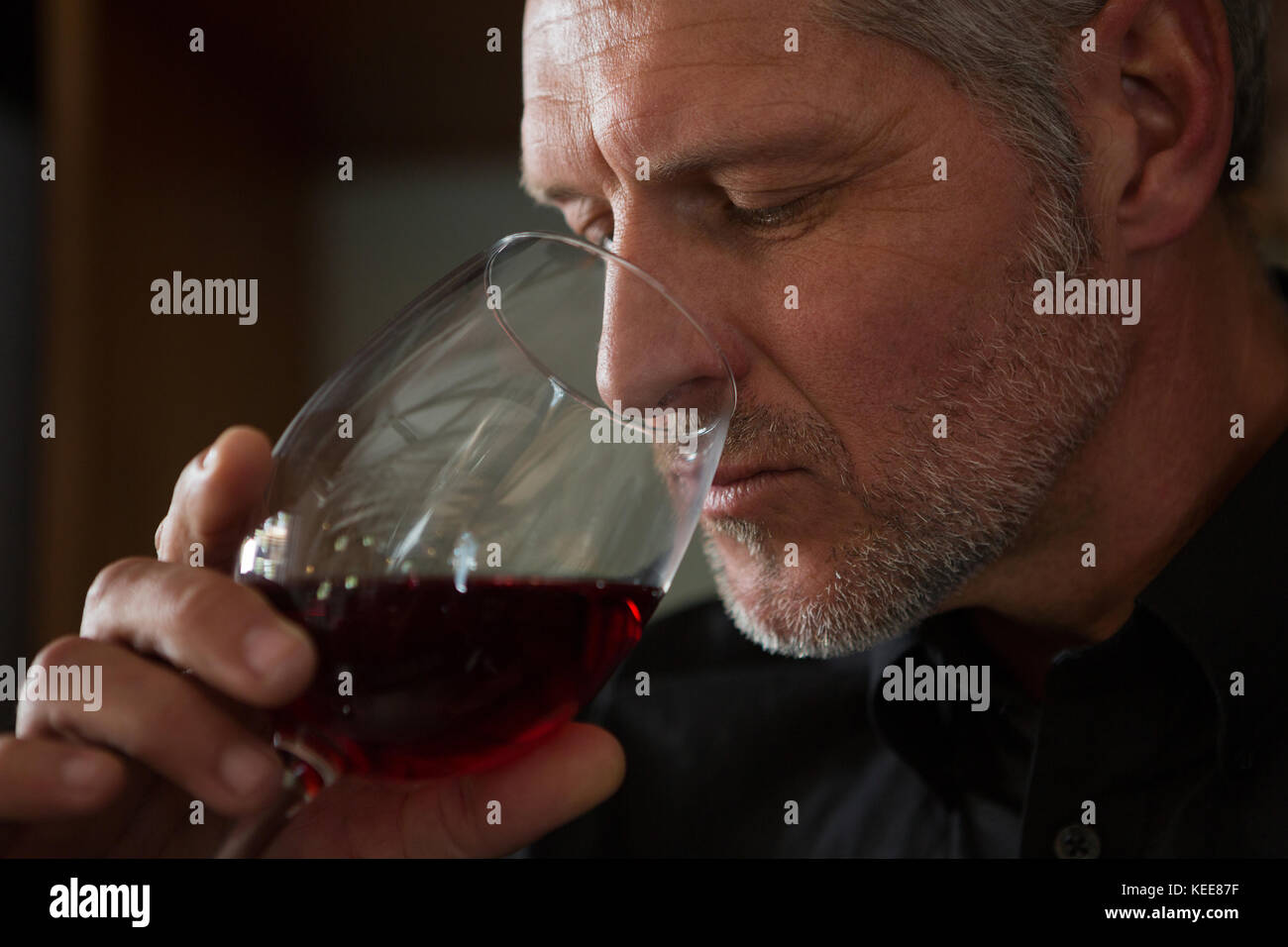 Waiter drinking wine in restaurant - Stock Image