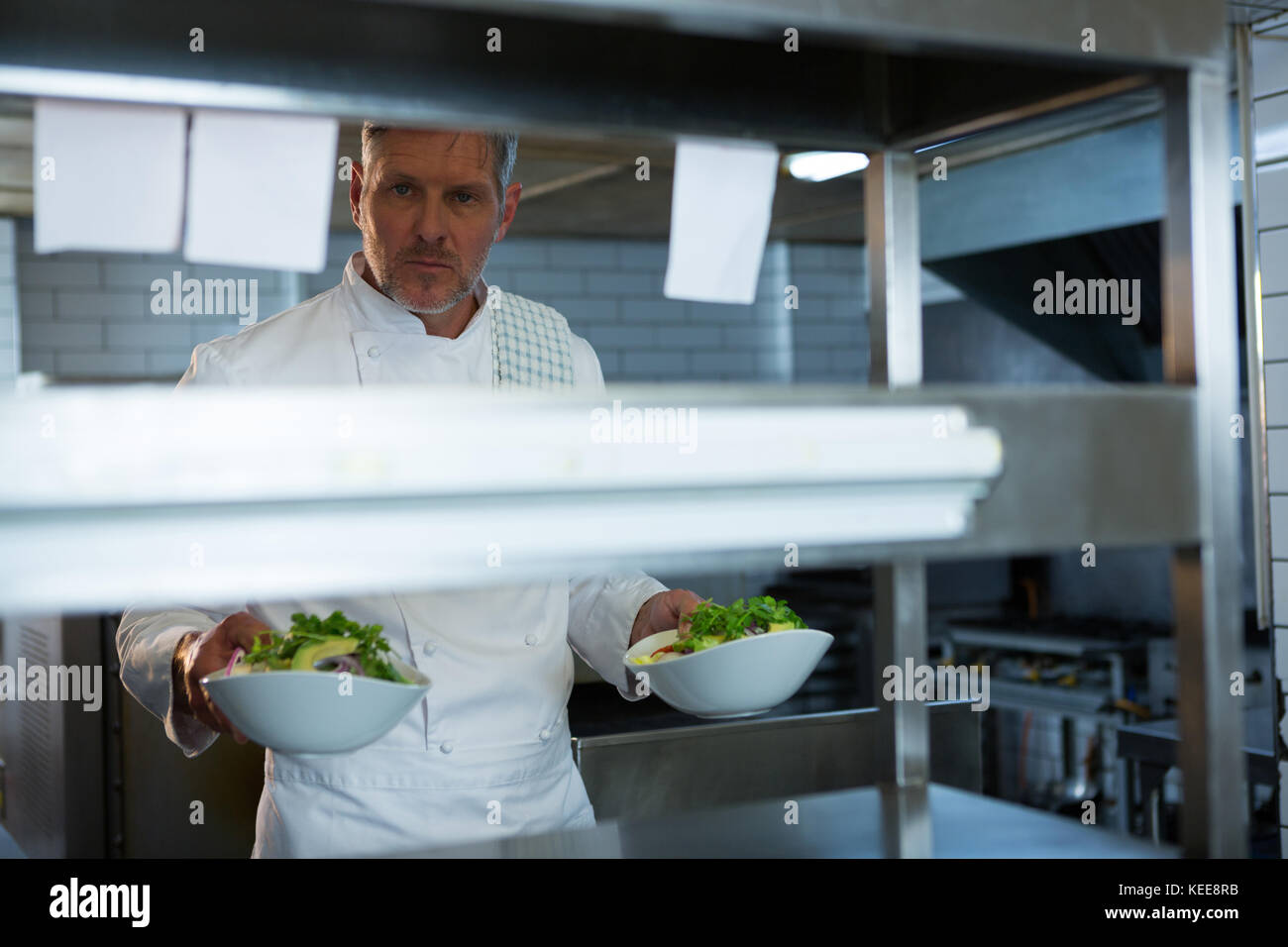Male chef holding food plate in the kitchen Stock Photo: 163812751 ...
