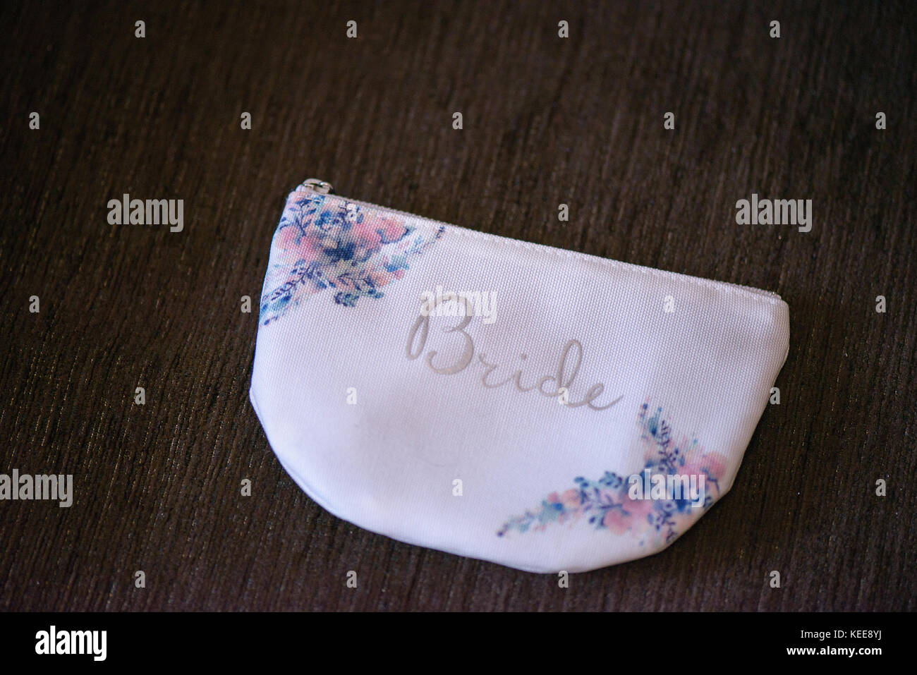 Delicate accessory with floral elements, a bridal purse with embroidered word 'Bride' in the front, against - Stock Image