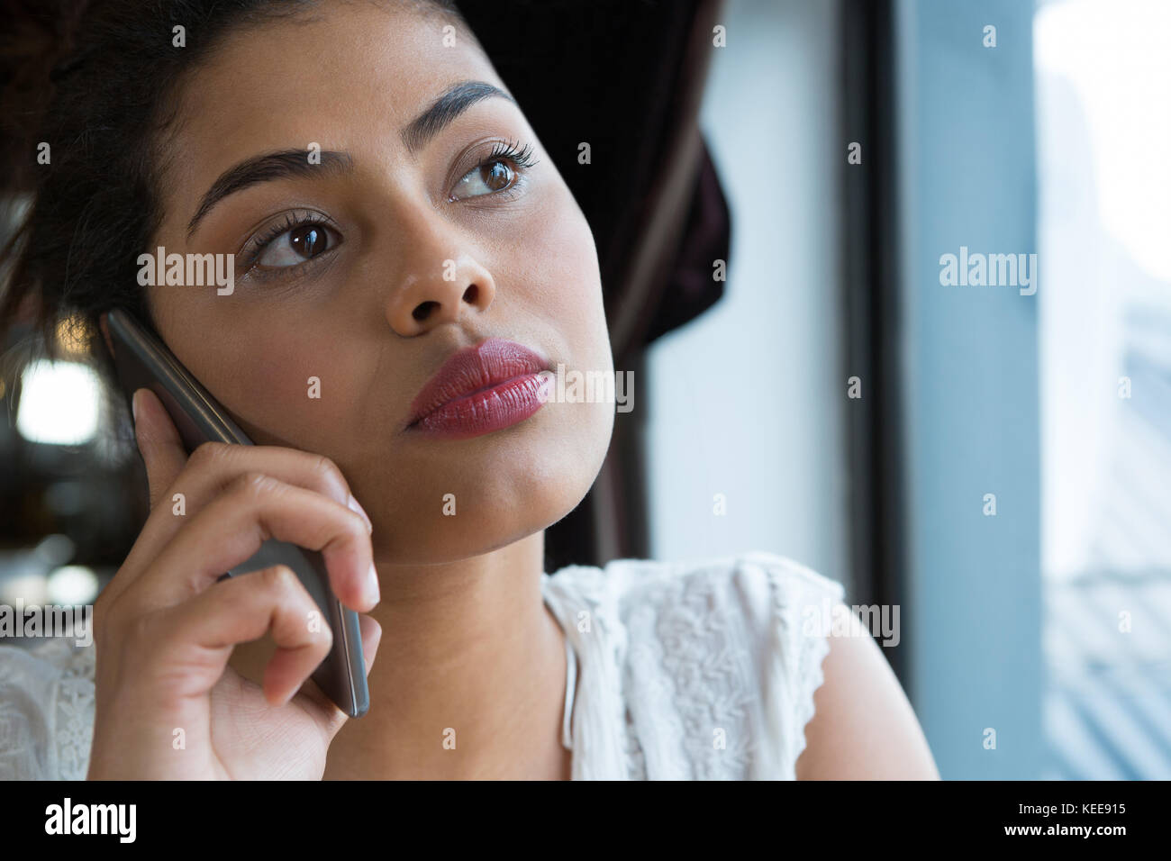 Woman talking on the phone at bar Stock Photo