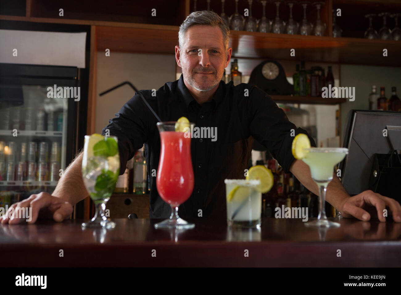 Portrait of waiter standing at bar counter - Stock Image