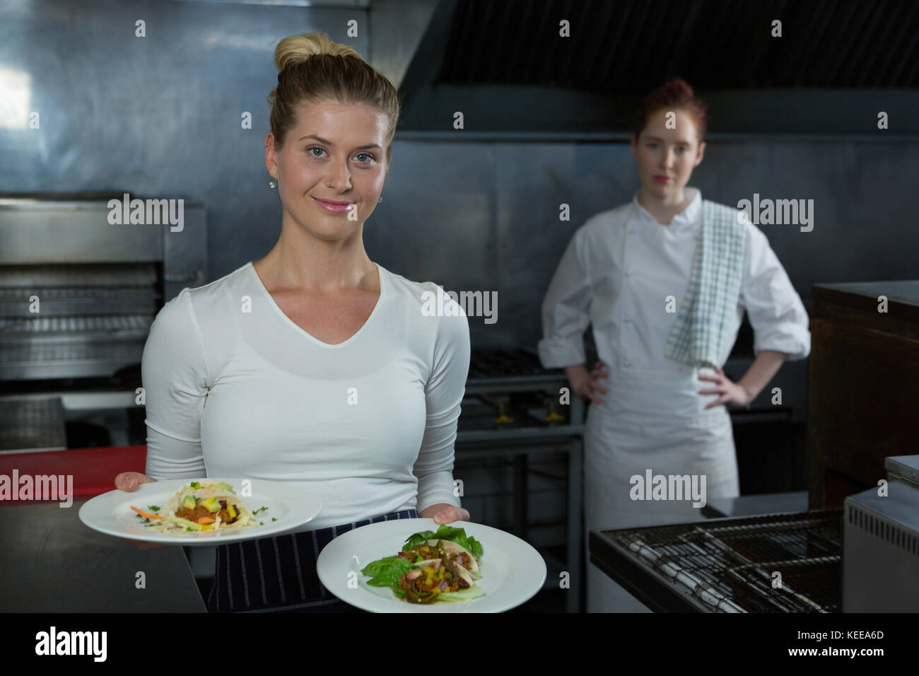 Woman Holding Plates In Kitchen Stock Photos & Woman Holding Plates ...