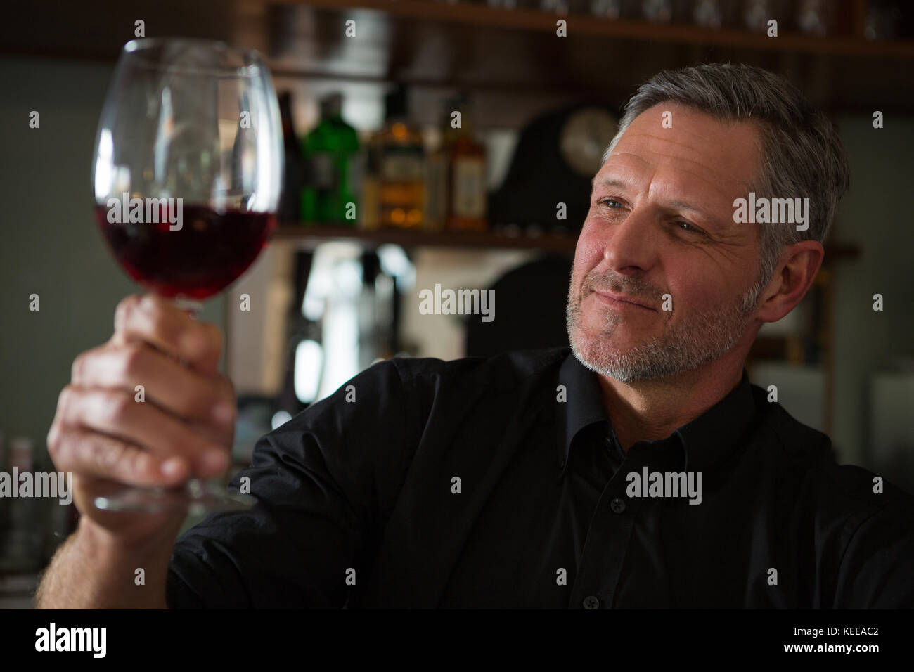 Close-Up of waiter looking at a glass of wine in restaurant - Stock Image