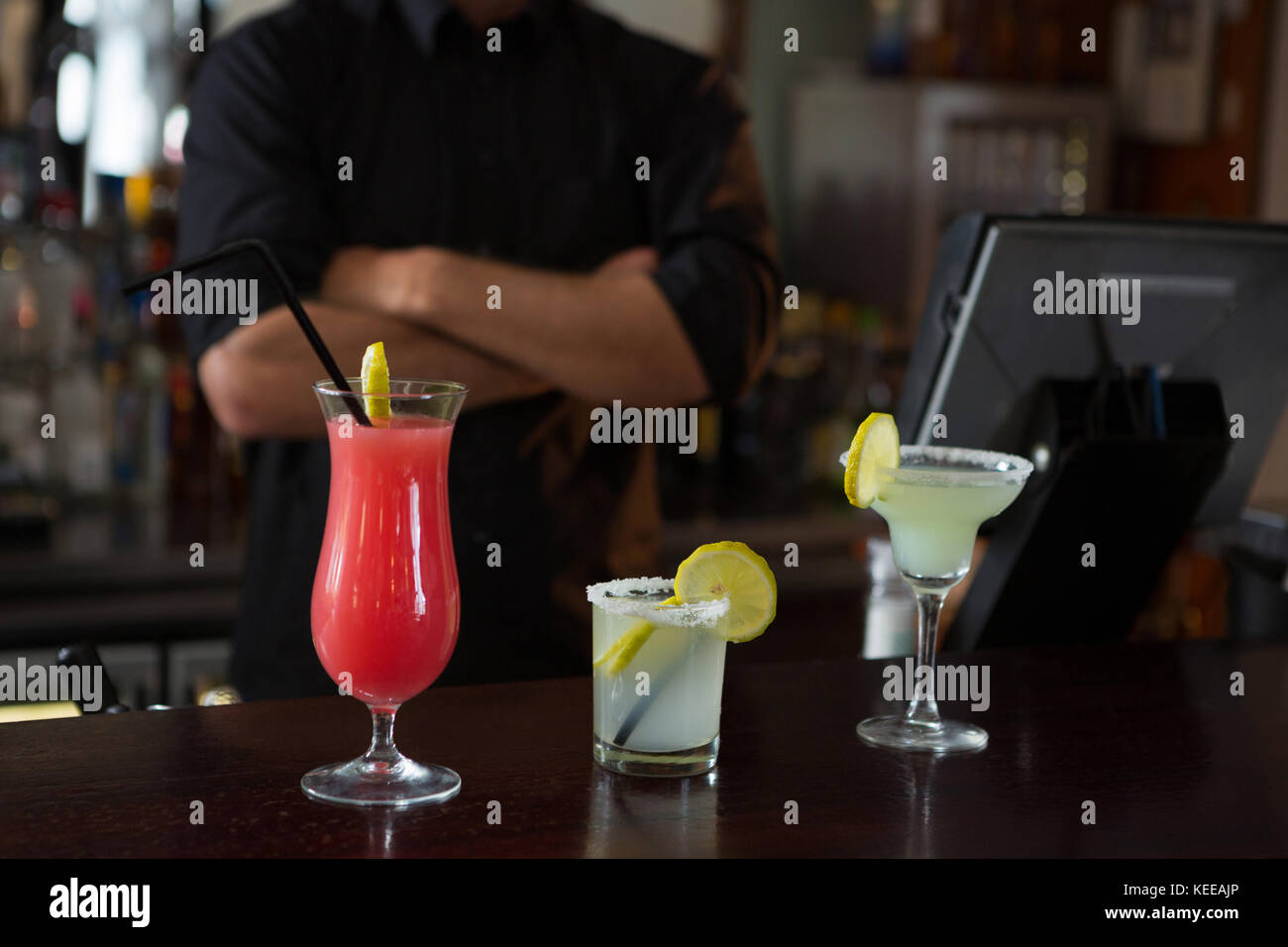 Mid-section of waiter standing at bar counter - Stock Image