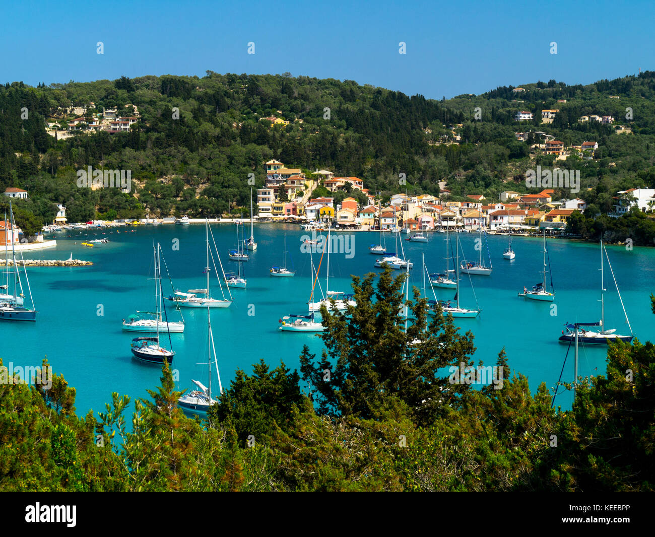 Yachts at anchor in the pretty and popular Lakka Bay, Paxos, Greece - Stock Image