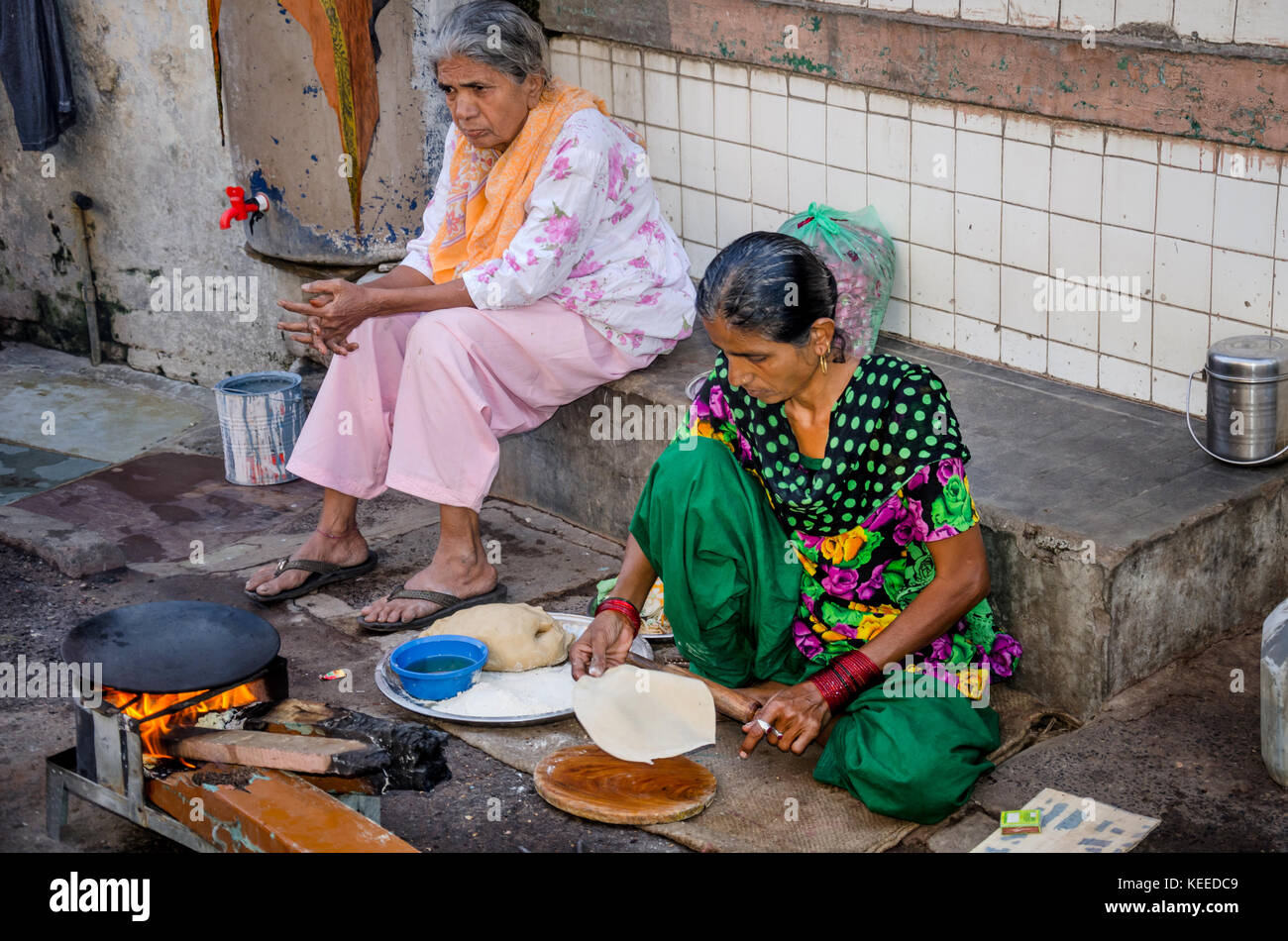 AHMEDABAD, INDIA - NOVEMBER 27, 2016: Muslim women cooking chapatti and food for family on the side of the street - Stock Image