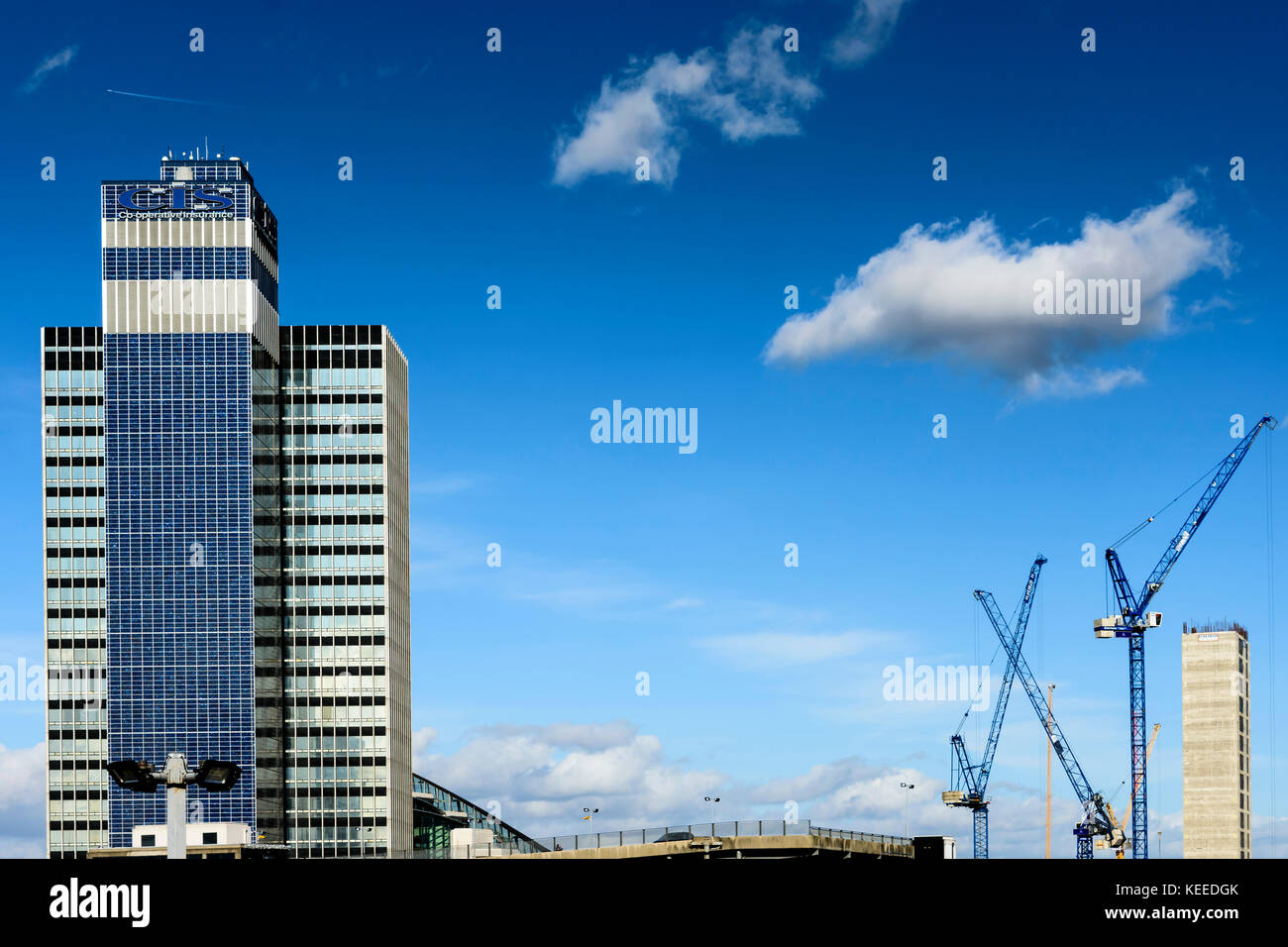 CIS Tower in Manchester with cranes and a deep blue sky, UK - Stock Image