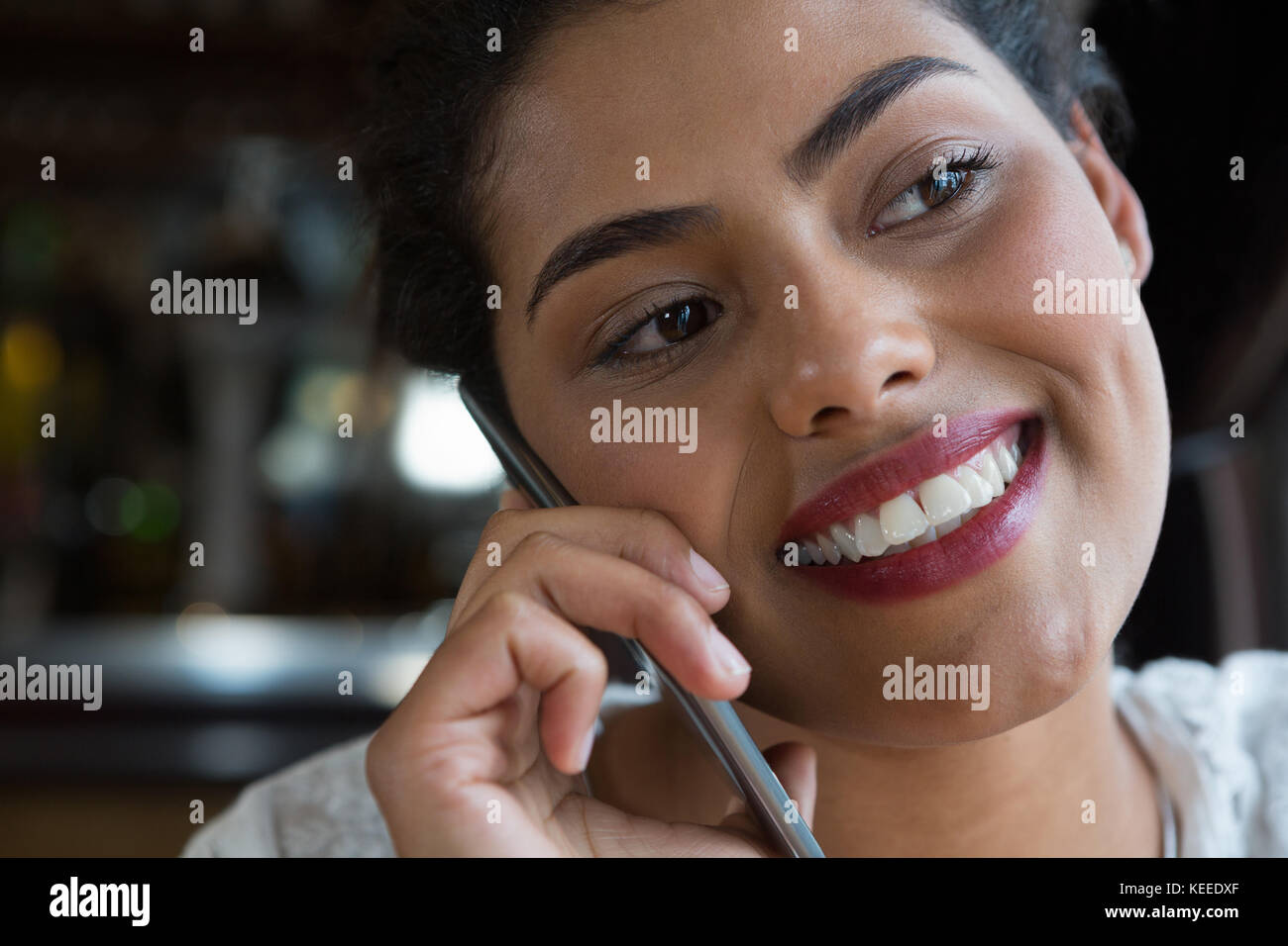 Woman talking on the phone at bar - Stock Image