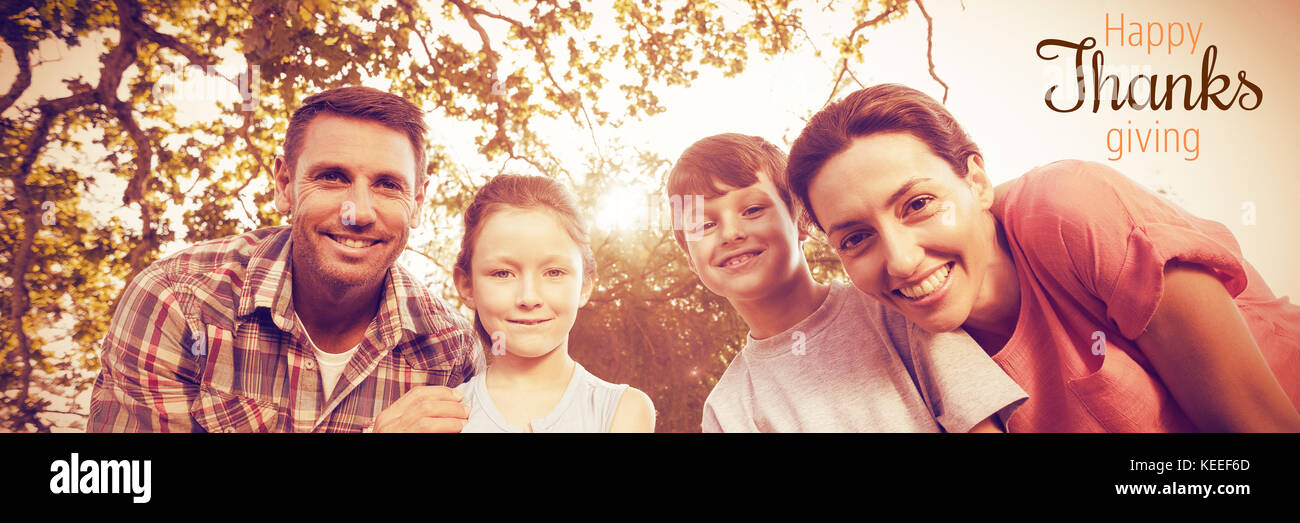 Thanksgiving greeting text against happy family smiling at park - Stock Image