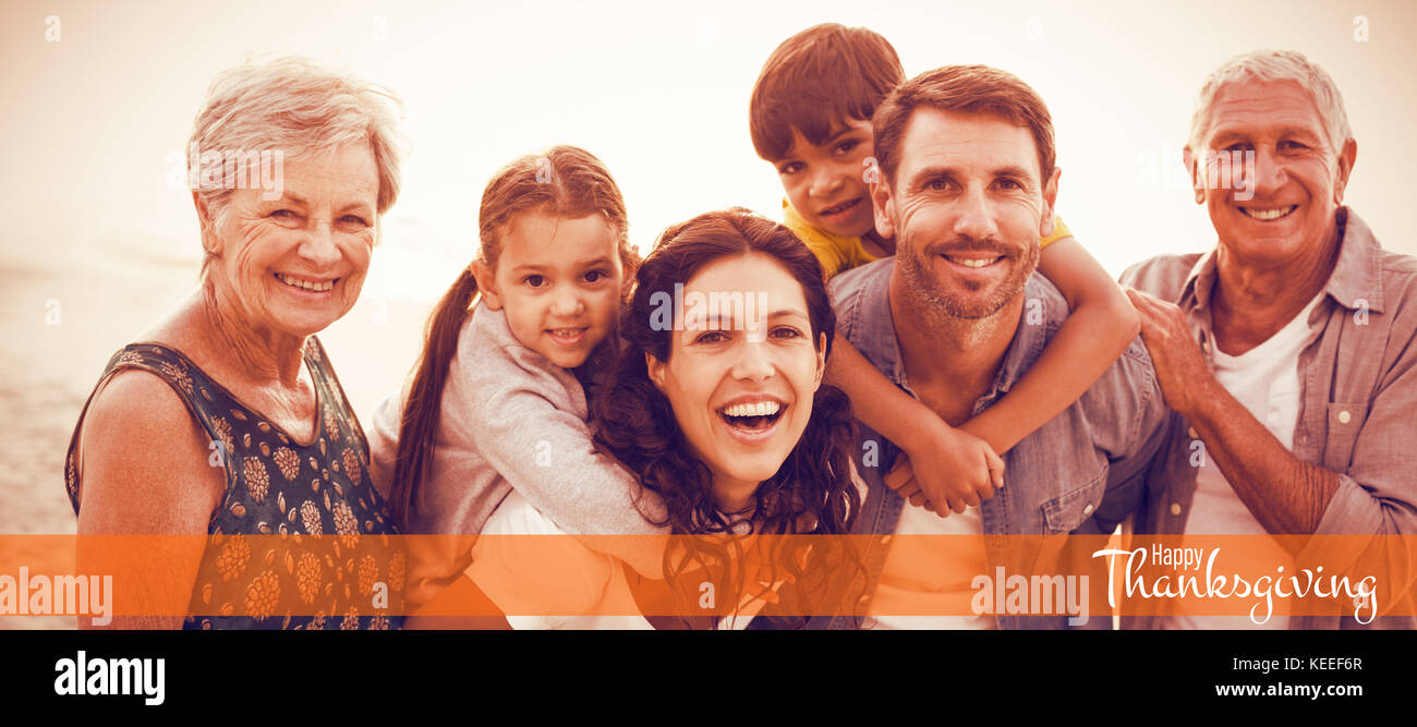 Illustration of happy thanksgiving day text greeting against happy family posing at beach - Stock Image